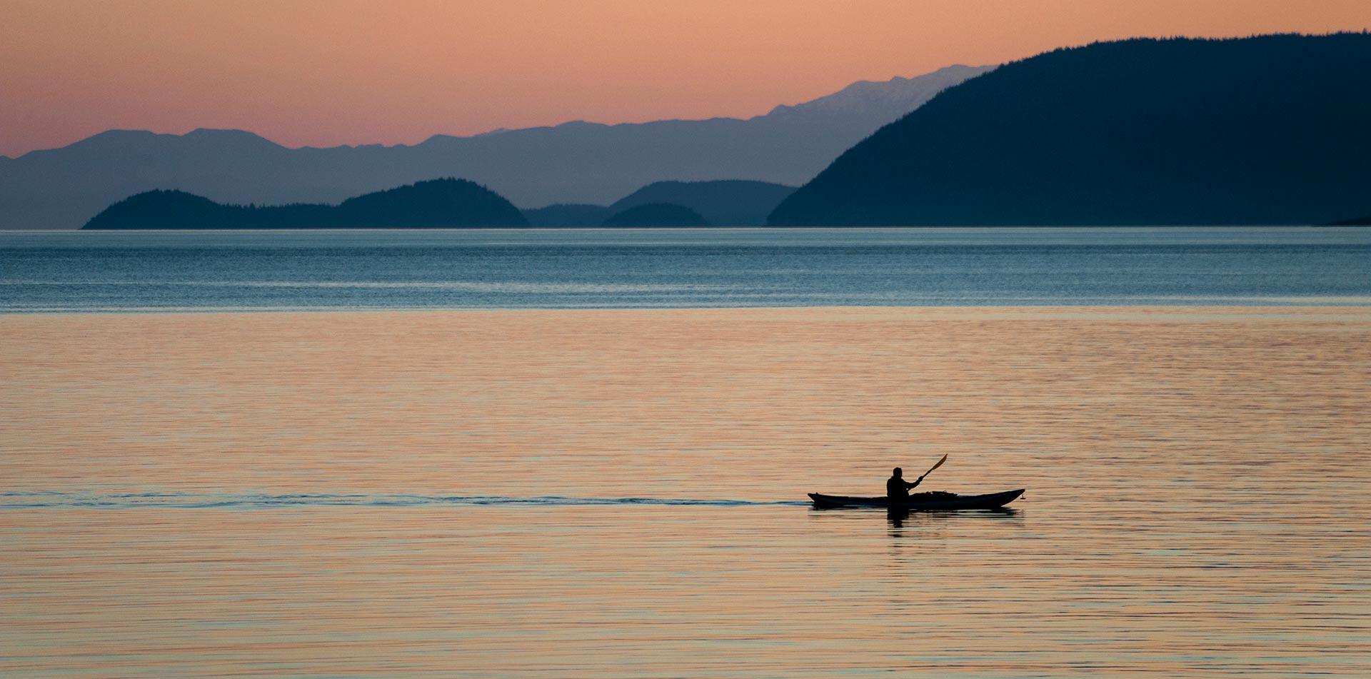 Man kayaking on water at sunset