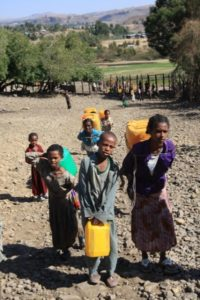 Ethiopian kids carrying jerry cans