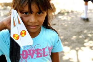 Young girl holding paper airplane in Ameya, Nicaragua.