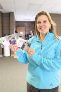 Julie Shriner from Emmanuel Community Church poses for photo with photos of her sponsored children