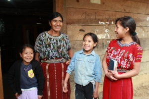 Elena and her family laugh together as they pose for photos in front of their home.