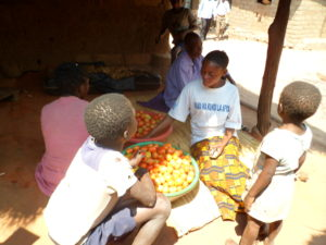 Maman Kichochi Makuu and her children in their home with a harvest of tomatoes