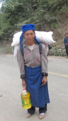 Woman loaded with rice bags and oil