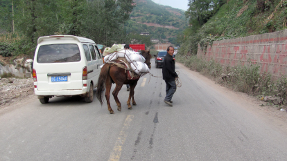 Man with donkey on road, loaded with relief food