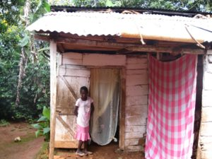 Young Haitian girl stands in front of her house