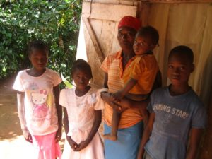 A Haitian mother stands with four children in front of their home