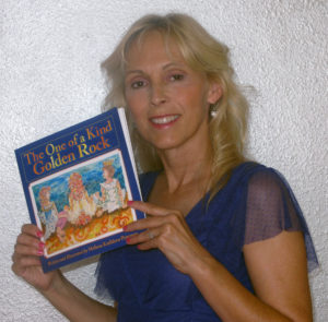 "Photo of Melissa Peterson holding her children's book ""The One of a Kind Golden Rock"""