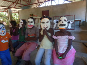 These sponsored children show off the masks they made at the afterschool program, Kids Club