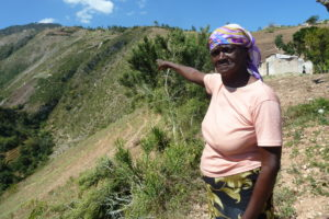 Madam Cristen stands on the rocky and narrow downhill trail point at both her garden and the community's current water source.