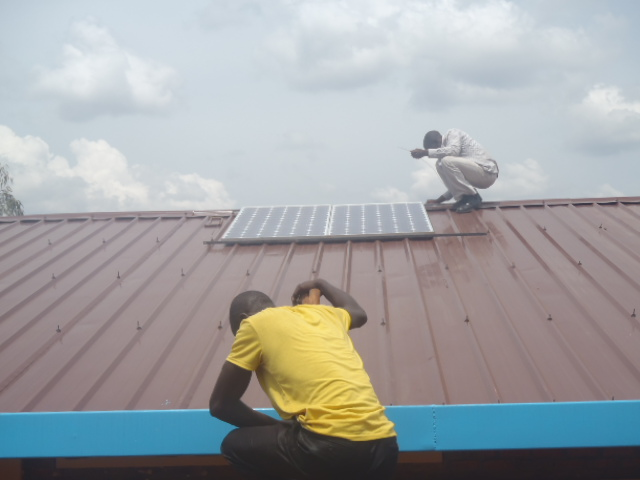 Men installing solar panel on school roof