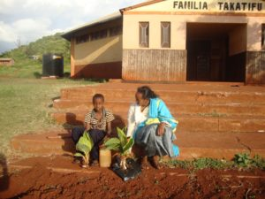 Guyo plants flowers at the church compound. He is pictured here with FH staff member Mary.
