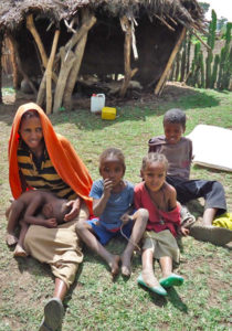 Tadelech and four of her children sit outside their home.