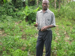 Farmer Dieuseul Petit shows off one of his chili peppers.