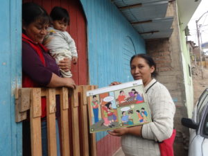 Carmen sharing health information with a mother and her baby.