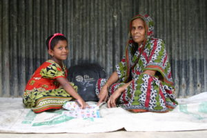 Ashiya (right) sits with her granddaughter. After receiving her literacy training, she knows that her grandchildren's education is of the utmost importance.