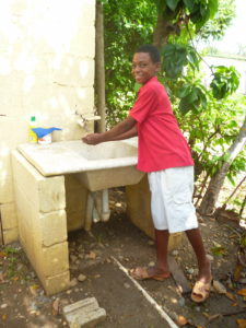 Adalberto washes his hands at his clean water faucet. This clean water has led to a healthier life for Aldalberto and his family.