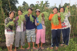 Martha and her Savings Group show off their bountiful harvest. Martha hesitated to join the group, but after witnessing her friend Naoi's (to her right) experience, she was convinced. Now, thanks to her vegetable supply, she no longer has to buy vegetables for her family.