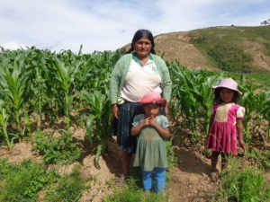Paulina and daughters standing near maize field