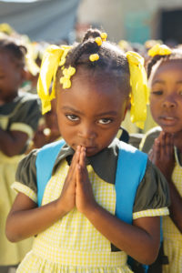 Girl with hands clasped in prayer