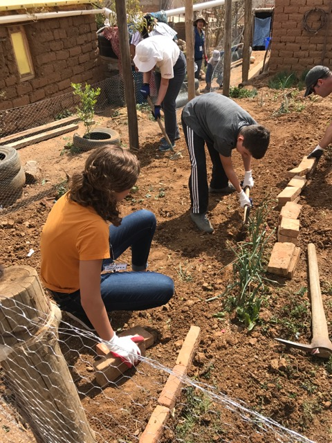 The team worked with community members to fence and plant a garden.