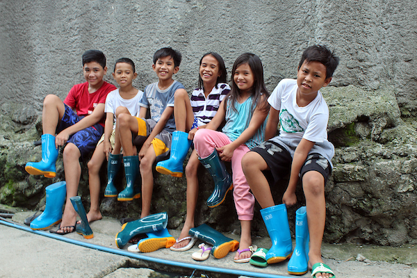 Kids in the Philippines smiling with rubber boots from Food for the Hungry.