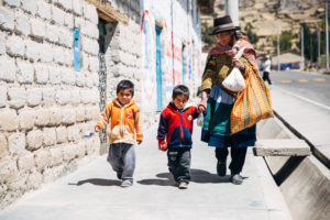 Peruvian mother holds the hands of her two boys.