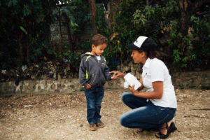 FH staff gives deworming tablet to a young boy in the Dominican Republic (DR).