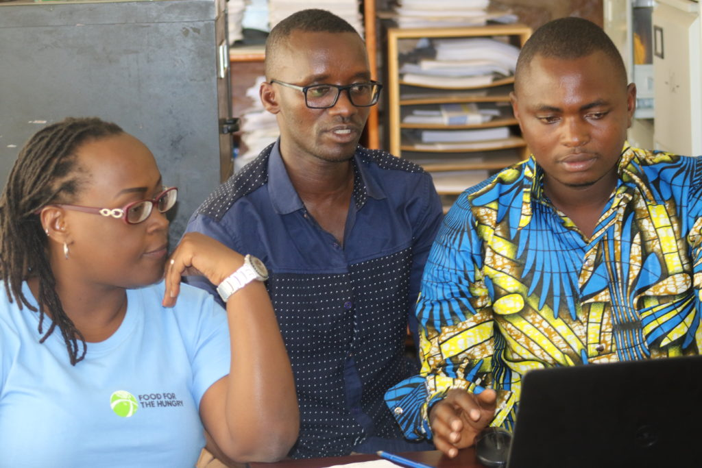 FH Burundi staff members gather around a desk to translate children's books into the local language Kurundi for the first time
