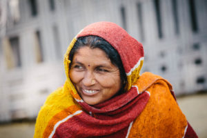 A woman in India with a red and orange headscarf smiles into the distance