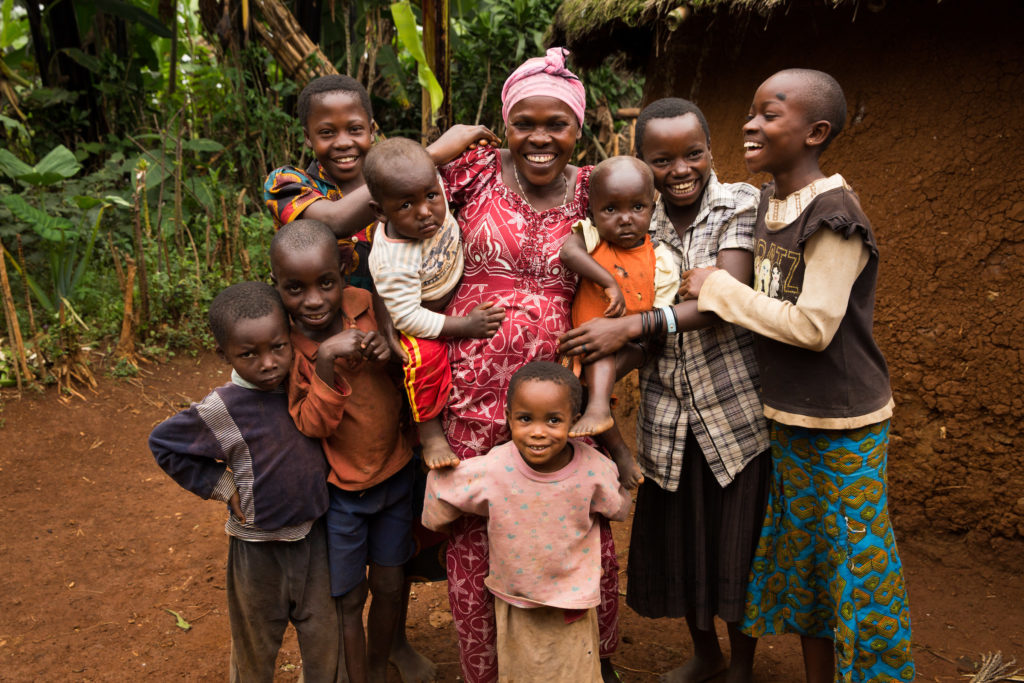 International Womens Day Photoessay - Mother in the Democratic Republic of Congo smiles next to her large family of children