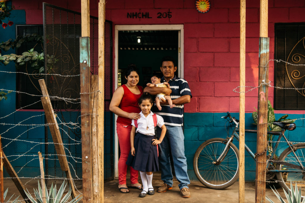 International Womens Day Photoessay - Family of four stands outside their red and blue brick house in Nicaragua