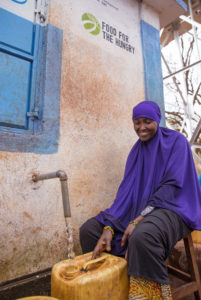 Kenyan woman in purple clothing gathers clean water from kiosk
