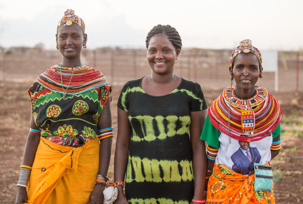 International Womens Day Photoessay - Three Kenyan women holding hands in traditional culture outfits and attire, with beaded necklaces and headbands