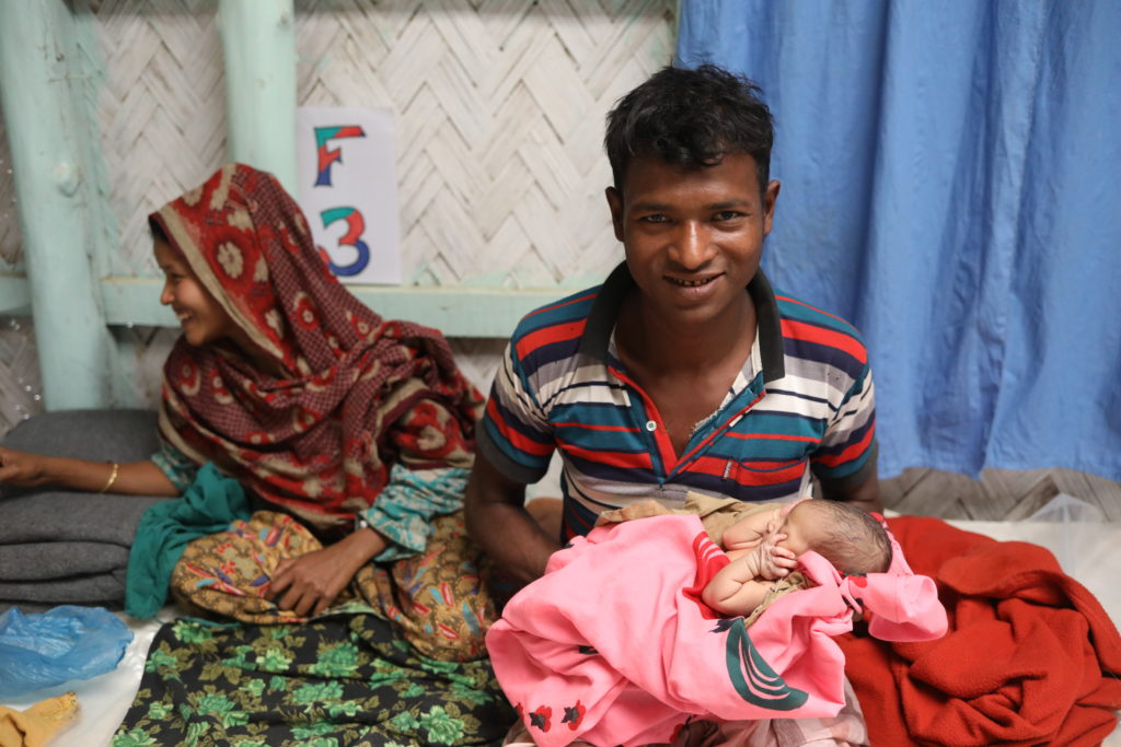 Mother in sari next to husband holding newborn baby wrapped in pink blanket