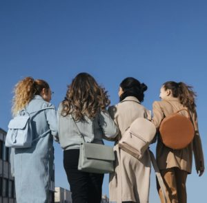 Four women standing with their back to us, wearing coordinating backpacks and purses from sustainable brands