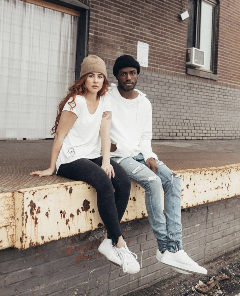 woman and man sitting on the side of a building wearing sustainable clothing brands