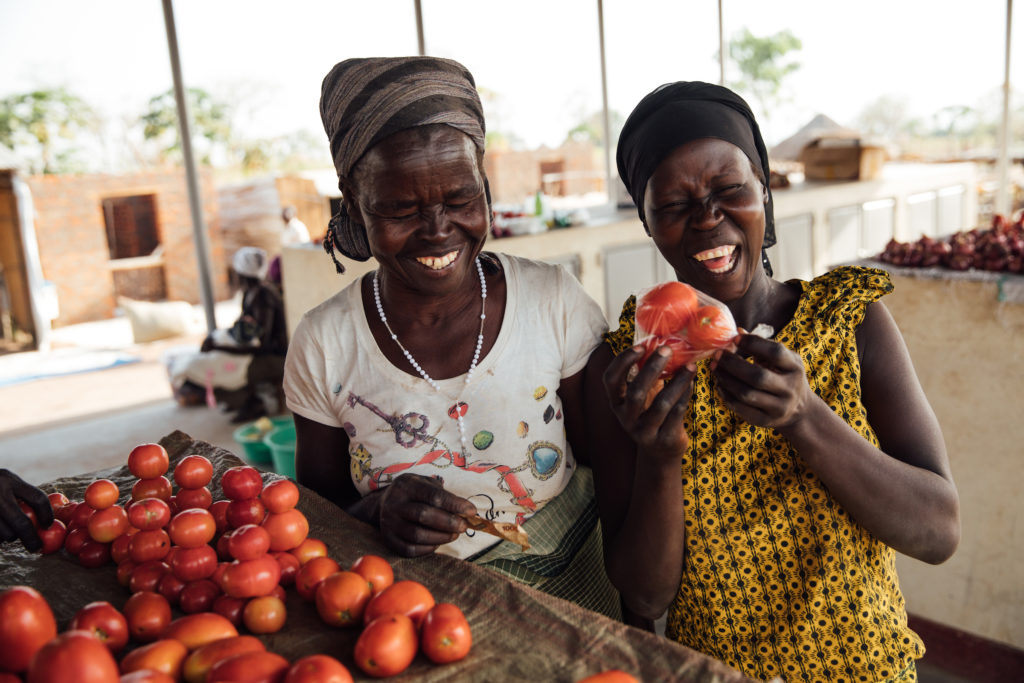 International Womens Day Photoessay - Two friends and women in Uganda smile in the local market next to ripe tomatoes
