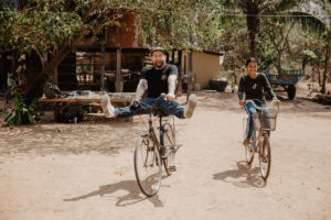 Child sponsor Doug Penick and sponsored child, Sopheap, ride bikes together in Cambodia.