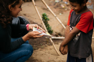 A humanitarian worker volunteer crouches down and shows a child sponsorship letter to a young boy.