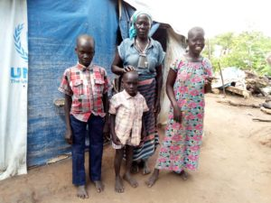 Cecilia, a South Sudanese refugee, poses with her three grandchildren outside an FH and UNHCR tent.