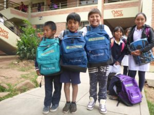 School children in Bolivia pose with their new backpacks and school supplies.