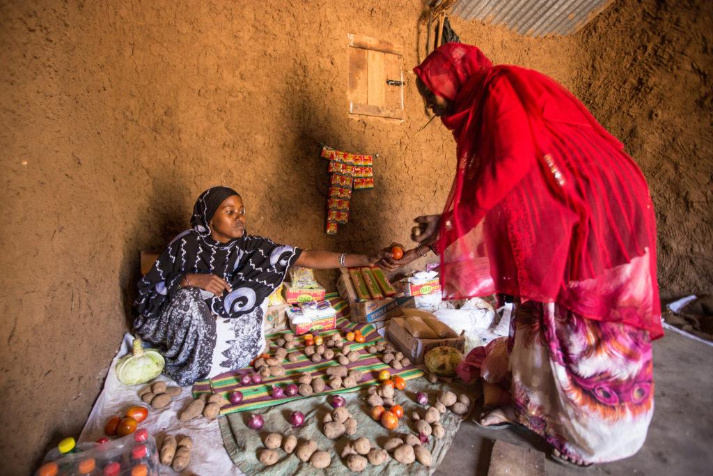 Kenyan mother sells fresh vegetables.