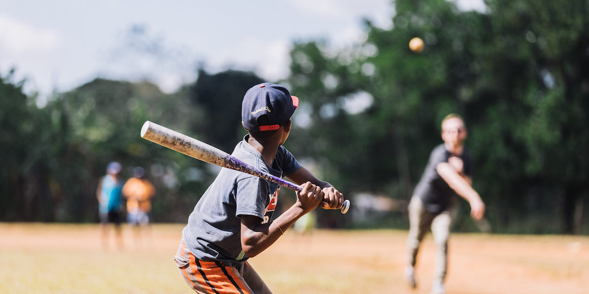 A young boy in the Dominican Republic holds a baseball bat, ready to hit the incoming ball.