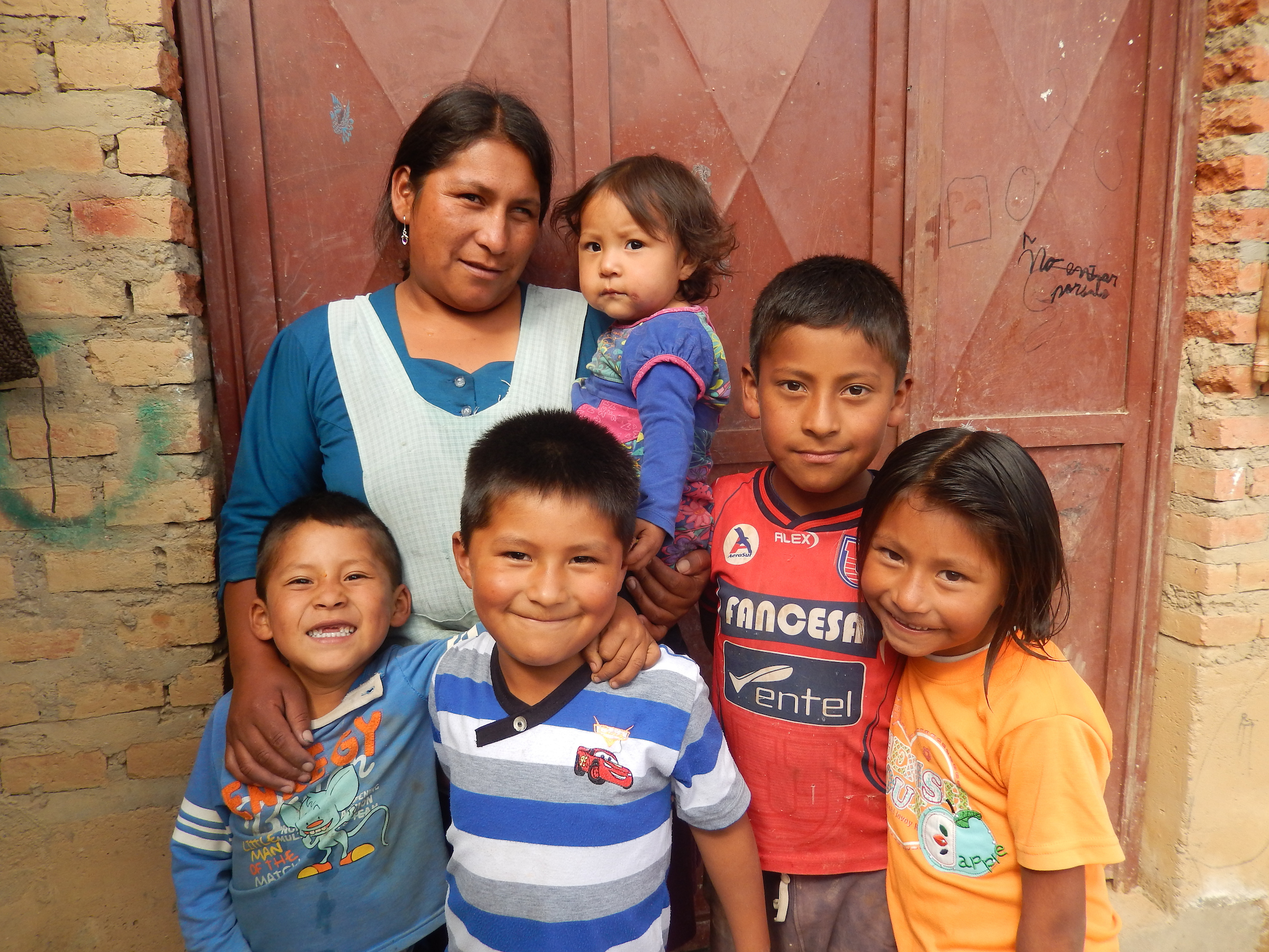 Bolivian family with mother and five children standing outside house