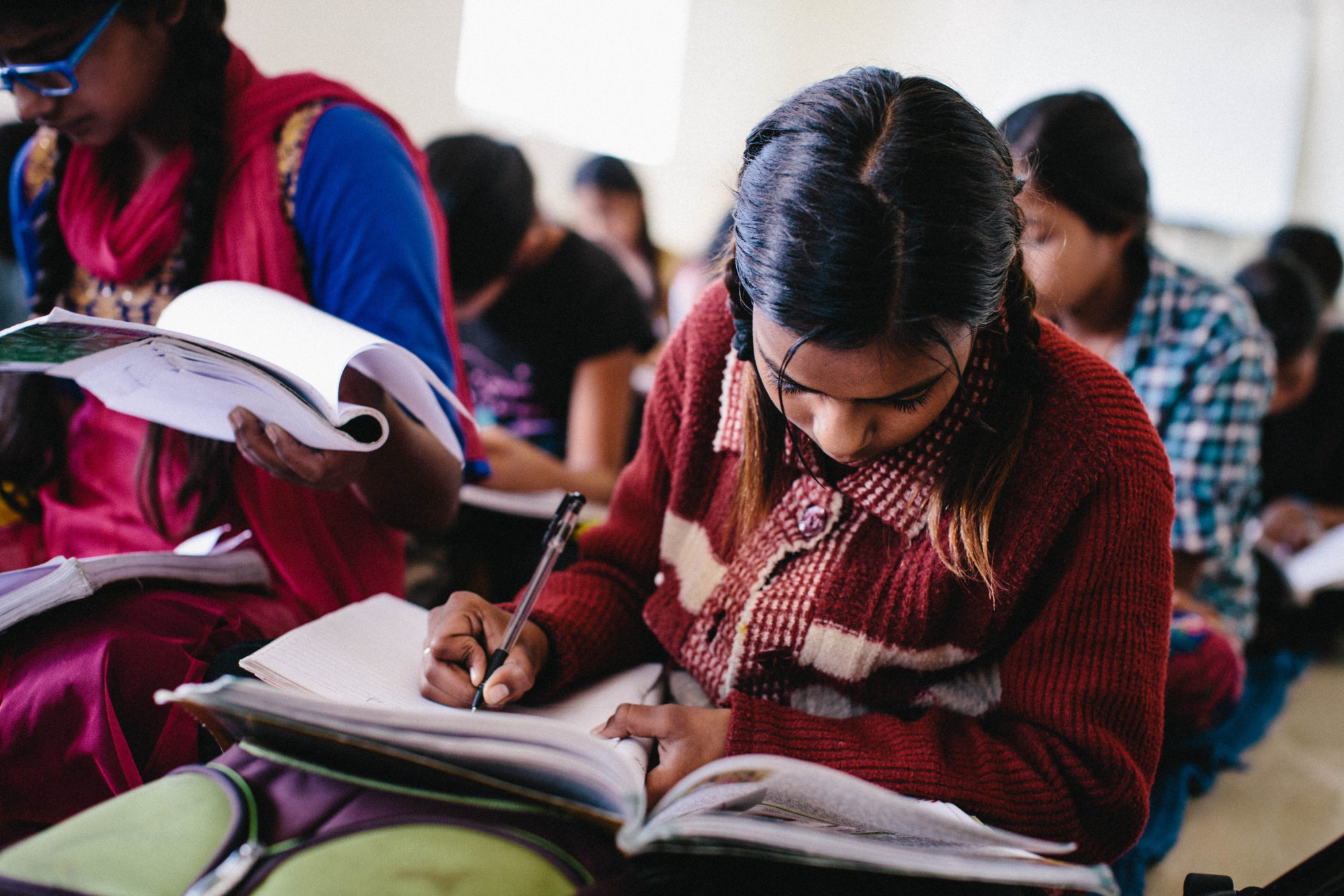 School girl in India wearing a red coat focuses on her studies and looks down at book