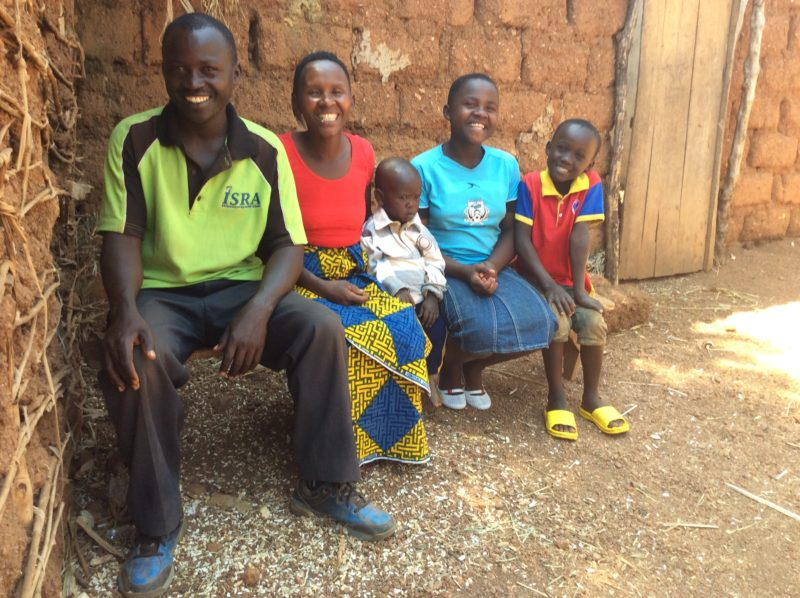 Man with wife and children in their home in Burundi