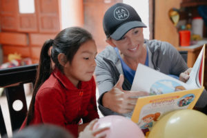 Erin Weidemann of Truth Becomes Her shares a Bible Belles book with her sponsored child, Evelyn, on her recent trip to Peru.