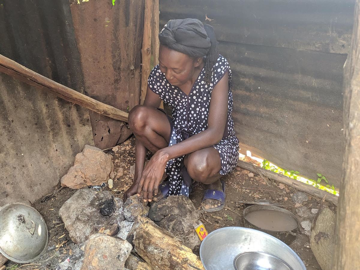 Haitian woman prepares fire for food