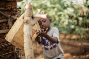 "Little boy washes his hands in Burundi from a ""tippy tap"" with a jerrycan."