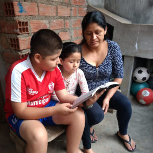Youth in Peru receive Bibles. Juan sits with his sister and mother reading the Bible